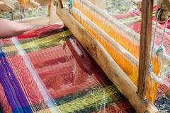 Weaving on a wooden loom Stock Photos