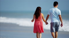 Young Hispanic family in colourful clothing spending leisure time by ocean Stock Footage