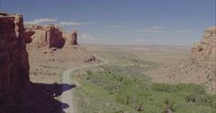 Aerial flying over desert highway showing with lone car driving in Canyonlands Stock Footage