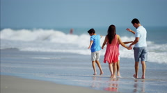 Young Latin American family in colourful clothing having fun on the beach Stock Footage