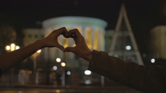 Young man and woman making hand heart gesture, showing love and compassion Stock Footage