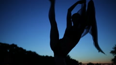 Gracefully woman silhouette in twilight dancing with windy flying cloth - stock footage