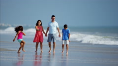 Happy Spanish children relaxing with parents by ocean Stock Footage