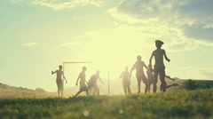 Boys are playing football in the sunshine day. Happy childhood and football in Stock Footage