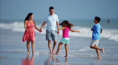 Attractive Spanish family in colorful clothing having fun on beach vacation Stock Footage