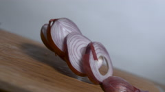 A sliced onion falls in slow motion onto a cutting board and separates Stock Footage