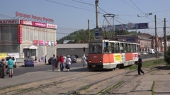 Orange tram starts from a stop and runs uphill the ascending track Stock Footage