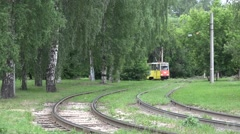Tram runs along curves in a green right-of-way Stock Footage