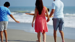 Young Spanish family in colourful clothing spending leisure time by ocean Stock Footage
