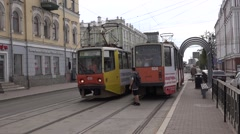 Two oncoming solo trams meet on segregated track near a stop Stock Footage