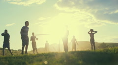 Simple poor farmer boys playing football on the background of a bright sunset in Stock Footage