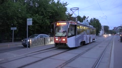 Sunset tram with electric lighting passes tracks crossing towards city center Stock Footage