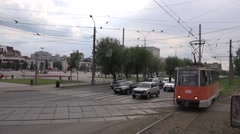 Old noisy tram slowly crosses a junction and meets an oncoming car (window shot) Stock Footage