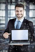 Sphere of icons against happy businessman showing laptop Stock Photos