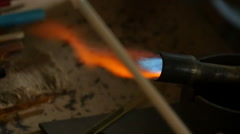 Glass blower heats glass for the manufacturing a toy 1 Stock Footage