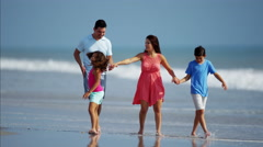 Young Hispanic parents and children having fun on beach holiday Stock Footage