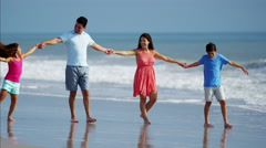Young Spanish family in colorful clothing having fun on the beach Stock Footage