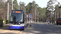Articulated tram turns right in Mezaparks cottage residential borough Stock Footage