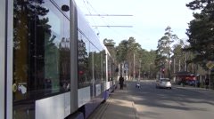 Articulated tram prepares to turn right in Mezaparks cottage residential borough Stock Footage