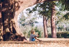 Boy with book sits under big tree in golden summer afternoon Stock Photos