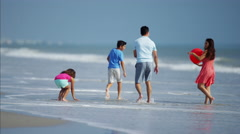 Latin American family playing together on beach vacation with red ball Stock Footage