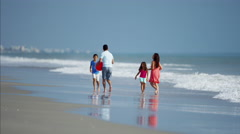 Hispanic parents enjoying holiday with children playing with red ball on beach Stock Footage