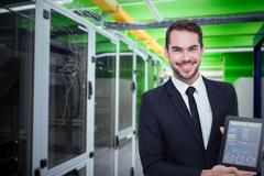 Smiling businessman showing his tablet pc against view of data technology Stock Photos