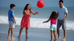 Fit Latin American family playing together on beach holiday with red ball Stock Footage