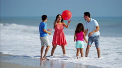Latin American family playing together on beach holiday with red ball Stock Footage