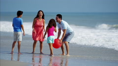 Happy Spanish family having fun with red ball on beach vacation Stock Footage