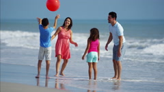 Laughing Hispanic family having fun with red ball on beach holiday Stock Footage