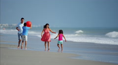 Young Hispanic family playing together on beach holiday with red ball Stock Footage