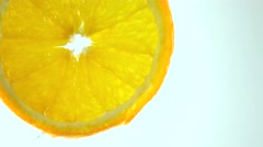 Macro 4K video of orange slice and dripping water against light background - stock footage