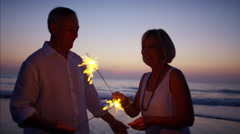 Retired Caucasian couple enjoying sunset with sparklers on their beach vacation Stock Footage