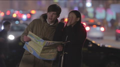 Young woman and man looking at map, searching for right way, lost in big city Stock Footage