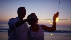 Caucasian seniors having fun at beach party with sparklers at sunset Stock Footage