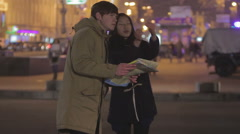 Female local helping male traveller to find destination, showing right direction Stock Footage