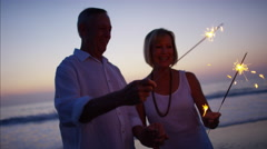 Mature Caucasian couple having fun with sparklers on the beach at sunset Stock Footage