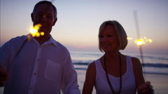 Loving Caucasian seniors having fun with sparklers on the beach at sunset Stock Footage