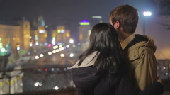 Young romantic couple in love hugging and looking at amazing night cityscape Stock Footage