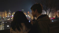 Young couple in love taking selfie and kissing at romantic date, night cityscape Stock Footage
