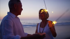 Caucasian seniors enjoying beach party with sparklers at sunset Stock Footage