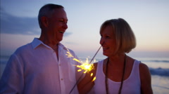 Retired Caucasian couple enjoying sunset with sparklers on beach vacation Stock Footage