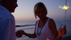 Retired Caucasian couple dancing with sparklers on the beach at sunset Stock Footage