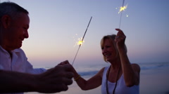 Mature Caucasian couple enjoying beach party with sparklers at sunset Stock Footage