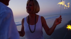 Happy Caucasian seniors dancing with sparklers on the beach at sunset Stock Footage