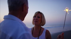 Senior Caucasian couple dancing with sparklers on the beach at sunset Stock Footage