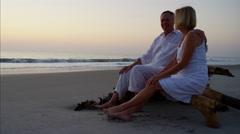 Mature Caucasian couple in white clothing on the beach at sunrise Stock Footage