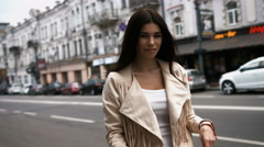 Portrait of a young brunette woman in white jacket posing with crossed arms Stock Footage