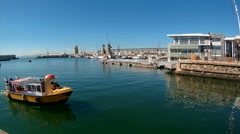 V&A Waterfront in Cape Town with passing tour boat Stock Footage